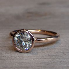A sparkly and substantial 7mm moissanite (equivalent in size to a 1.25 carat diamond) sits in a handmade tapered bezel on a 2mm round hammered