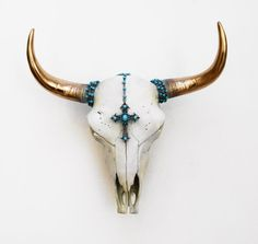 With horns in bright gold, this buffalo skull has gone up market with his golden assets. El Toro is dressed in natural tones of bone and grey.