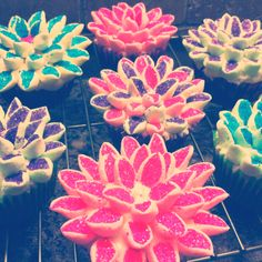 Marshmellow flowers !  Cut the marshmellows diagonally in half. Get different sugar colours, put in separate bowls for each colour. Dip the cut marshmellows in the different sugar colours and put onto cupcake around starting from the outside. Don't forget to ice the top of the cupcake before placing marshmellows on! Enjoy