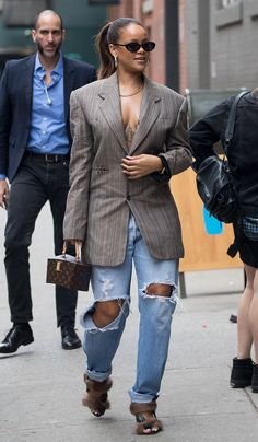 6f5dec16a04 Slide 7 of In Rihanna wore an oversize blazer and baggy jeans with furry  heels. She carried a Louis Vuitton box clutch.