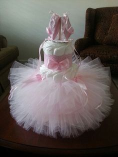 This cake is for the ultimate baby ballerina. Multiple yards of tulle was used to create the beautiful flowing tutu that encircles the bottom two tiers. Beautiful pink ribbon accent the top of the tutu skirt. The ballerina slippers that sit on top are on their tip toes in a perfect ballerina stance (not attached to cake)The shoe ties flow freely down the cake and can be positioned as you wish. This beautiful cake towers 17 inches tall and will be the talk of your event. The cake is made of…