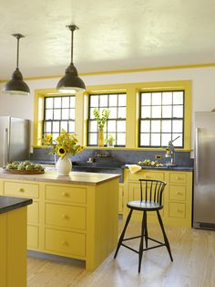 An easy way to unify the look of a kitchen is to use one color for cabinets and trim. Here, the same cheery yellow on the base cabinets extends up the wall to the casings and crown, contrasting with darker windows.