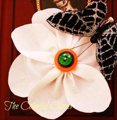 Happy Halloween! Glow in the Dark Flower with orange, purple and green button with a black glittery butterfly.