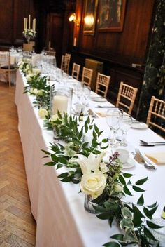 Thornton Manor wedding flowers - Foliage garland, votives including lilies, roses and chrysanthemums, and hurricane vases. - Flowers by Laurel Weddings