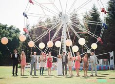 Wedding party photo with a Ferris wheel and big balloons.