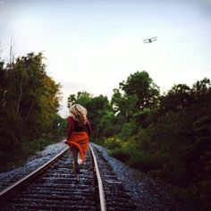 Chica corriendo a través de las vías del tren
