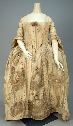 METALLIC BROCADE ROBE a la FRANCAISE, FRENCH, 1774 - 1793. Cream silk taffeta having woven blue stripe, brocaded with polychrome silk floral with blue and magenta metallic threads, sacque back open robe having elbow length sleeve with double fan cuff, decorated with swags of pleated net with metallic stripe and cloth flowers with glass beads, linen lined bodice with back laces, silk cuff and hem facings, matching petticoat and stomacher with metal stays.