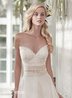Poppy wedding dress by Maggie Sottero | Romantic lace and a soft Vicenza organza combine to create this timeless A-line wedding dress, with sweetheart neckline and wide Soft Shimmer satin belt, glittering with Swarovski crystals, at the waist. Finished with half corset and half zipper closure.