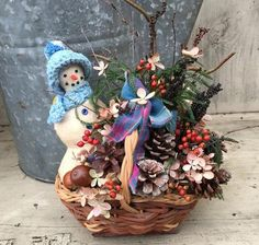 Primitive snowman with crochet hat and scarf in vintage basket with dried flowers centerpiece.