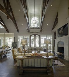 """""""For the living room, I designed a huge chandelier that fits to the scale of the space. At the same time, I designed the large pot rack over the kitchen island. I wanted those two large fixtures – the chandelier and the pot rack – to imitate and play off of each other, helping to unite the entertaining area.""""   - ELLEDecor.com"""