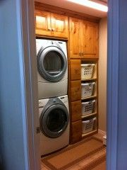 Showing this to Dave tonight!  For Mother's Day, he said he would put in cabinetry in my laundry room.  This is EXACTLY what I want!  I actually love the stacked washer and dryer.  Perfect laundry room..love the basket shelves & all the cabinets to hide laundry detergent and for extra storage!