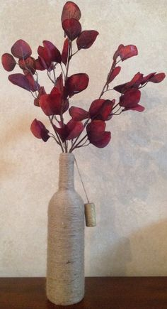 Simple but elegant, this wine bottle vase with decorative dongal is ideal for any color scheme.