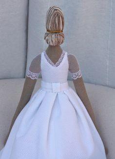 La espalda escotada a pico. El pelo recogido en un moño, y un adorno dorado.
