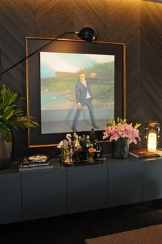 Casa Cor 30 anos   Almoço de sexta - projeto de uma sala com uso de painel de madeira e móveis pretos. a iluminação destacou bem os móveis e para decorar quadros, vasos com flores e livros