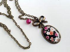 Collier, en bronze, cabochon ovale, petites fleurs sur fond noir, nœud, perle fuchsia. Matériaux utilisés: , BronzeVerre