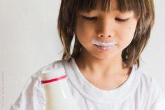 Cute little boy face with yoghurt mustache by nabi | Stocksy United