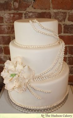 White wedding cake with edible pearl accents.
