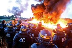 Riot police stand guard behind a fire as refinery workers blockade the oil depot in Douchy-Les-Mines, France