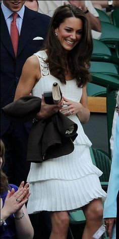 Kate at Wimbledon in a cascading or tiered knife pleated white day dress with cut-out strap detailing. She has great style.