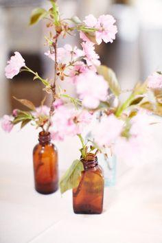 Vintage bottles filled with pink blossom