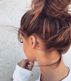 Tatto Ideas 2017  petit tatouage femme oreille rose aux contours noirs chignon décoiffé fille