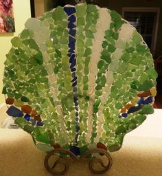 I wanted to display all the sea glass my daughter and I find on our beach a better way.  I found this glass dish for $2 at a local thrift shop and created this with hot glue and our sea glass!