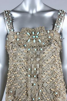 An opulent be-jewelled orientalist cloth of silver evening gown, probably Callot Soeurs, 1907 and altered in the 1920s, columnar with gold embroidered filet lace over-dress studded with cabochon turquoise stones and pearls, the hem with deep band of Egyptian papyrus blooms