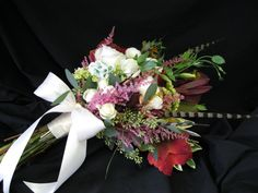 Loose arm bouquet created with peonies, ranunculus, spray roses, astilbe, green mini hydrangea, maple leaves, and other fun greenery with pheasant feathers and the Bride's Great Grandmother's handkerchief folded like a rose incorporated into the bouquet.