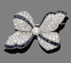 A diamond and sapphire bow brooch  Centrally-set with a collet-set brilliant-cut diamond, within a surround pavé-set throughout with similarly-cut diamonds and highlighted with four calibré-cut sapphire borders, diamonds approx. 4.10cts total, length 5.6cm, fitted case by Garrard & Co Ltd