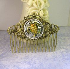 Something unique- a handmade antique brass floral filigree hair comb embellished with a swimming sea turtle. It measures 3 long and would be lovely for a beach wedding, formal or party. Sea Turtle Art, Hair Comb Clips, I Believe In Angels, Wedding Summer, Cat Wall, Cross Pendant, Antique Brass, Filigree, Black Silver
