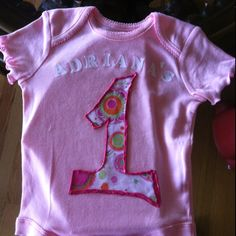 Shirt to eat first cake.  Iron letters, printed fabric cut into number one shape, fabric glued on and outlined in fabric puff paint so edges don't fray or come loose.