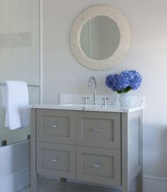 source: Kitchens by Deane    Stunning bathroom with gray bathroom vanity with calcutta marble countertop and polished nickel gooseneck faucet. Cream round mirror over gray bathroom cabinet and glass shower.