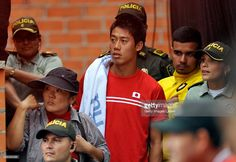 Kei Nishikori watches scorted by police officers during the Davis Cup World Group Play-off singles match between Alejandro Falla of Colombia and Taro Daniel of Japan at Club Campestre on September 20, 2015 in Pereira, Colombia.
