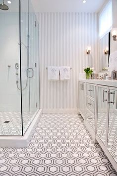Bathroom with black and white penny round mosaic tiles used to make a hexagon pattern on the floor, mirrored cabinet doors and grey and white striped wallpaper. Great for a large bathroom or to give interest to a small powder room