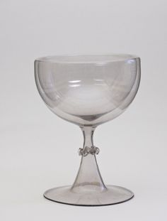 FACON de VENISE TRICK GOBLET.  1650. The goblet has a double-walled bowl on a narrowing stem applied with a pincered collar. The glass has a grayish-lilac tint. It is called a trick glass because inside bowl can be filled with wine through a small hole in the stem; the hole is then plugged with wax. A person could seem to drink all night without the glass becoming empty.  Or a person could go up to someone and pretend to spill it and nothing would happen.