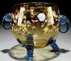 A continental enameled yellow glass center bowl, having a spherical body, applied birds, insects and branches, applied blue elephant masque handles and branch feet. Czechoslovakia, circa 1876-1925