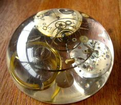 """""""My Grandfather's broken mechanical watch embedded in resin.""""  (The world's best steampunk paperweight!)"""