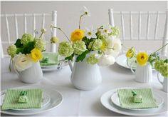Mesa de jantar decorada. Arranjo de mesa com tons de verde. Jarro de flor para decorar a mesa.