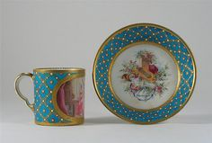 A jewelled Svres style cabinet cup and saucer, the cup painted with a panel depicting musicians, the saucer with instruments of the Arts, on a gilt bleu cleste ground, inscribed 'Donn par moi le Roy La Grande duchesse de Saxe', interlaced 'Ls' enclosing 'A', 19th century. (2)