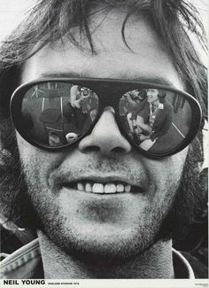 An awesome portrait poster of Neil Young in sunglasses at Oakland Stadium in…