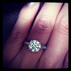 Loving this round brilliant solitaire with two side baguettes