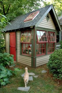 Cute garden shed with bright red door and lots of windows.