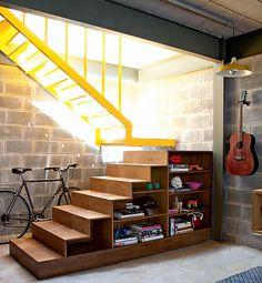 """A parte amarela, de metal, da escada foi projetada para parecer """"flutuar"""", enquanto a de baixo funciona como estante. """"O objetivo era dar leveza a esse volume"""", explica o arquiteto Tito Ficarelli, cujo escritório Arkitito desenvolveu a peça"""