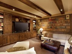 Is it a library or a media room? Don't let the trompe l'oeil bookshelf wallpaper fool you. This cozy living space features a custom entertainment center with built-in shelves and rustic exposed beams to match. A plump sectional boasts seating around an oversize leather ottoman – perfect for movie nights.
