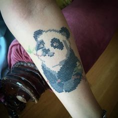 Cross stitch style panda bear tattoo on the inner forearm....