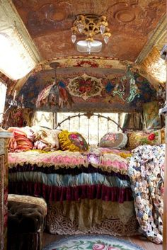 Antique bed with gypsie boho chic style; layers of small scale prints and paterns, florals, lace, and mismatched vintage chandeliers and pillows help create this look!