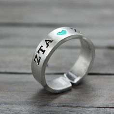 """This charming hand stamped Zeta Tau Alpha Ring will keep your letters close. Features & Measurements: ♥ 14 Gauge Aluminum ♥ 1/4"""" Wide ♥ Easily Adjustable"""