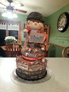 Cammo Hunting themed Diaper Cake.   Made the signs on my Cricut.   Used burlap ribbon and duct tape and special delivery washi tape around the diapers.   Found a little stuffed scarecrow and put the Cammo hat I knit for the baby on it.   I shredded a paper bag and put paper leaves around the layers.  Almost too cute to give away.