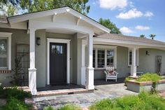 Try a portico. A portico is simply a small roof over the entry, braced by two columns. It is a defining feature that gives shape to the facade and also serves the practical purpose of a shelter from weather at the front door.