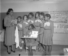 African American Girl Scouts listen to instructor talk about first aid, ca. 1955.    On March 12, 2012, Girl Scouts of the USA celebrated 100 years.